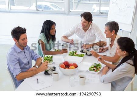 Business people eating lunch together in the office - stock photo