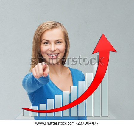 business, people, economics, success and gesture concept - smiling young businesswoman pointing at you over gray background and growth chart - stock photo