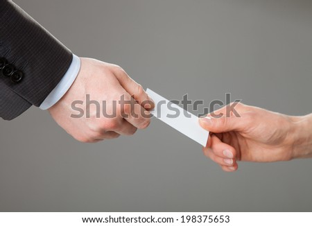 Business people exchanging business card on grey background - stock photo