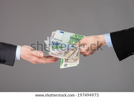 Business people exchanging money on gray background - stock photo