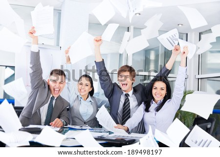 business people excited happy smile, throw papers, documents fly in air, businesspeople sitting at office desk hold hands arms up, success team concept after sign contract - stock photo