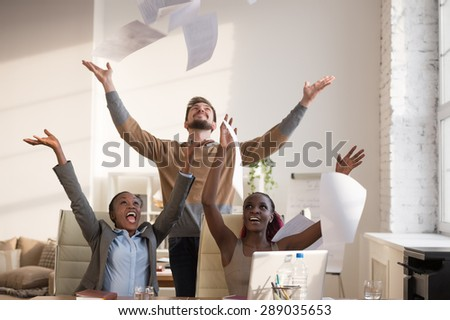 Business people excited happy smile, throwing up papers, documents fly in air, businesspeople sitting at office desk hold hands arms up, success team concept  - stock photo
