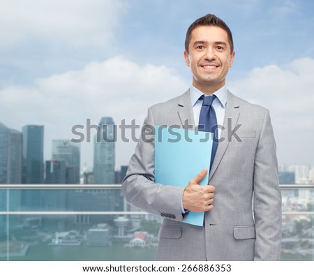 business, people, finances and paper work concept - happy smiling businessman in suit holding folder over city background - stock photo