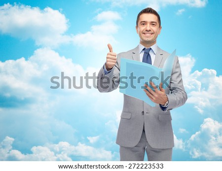 business, people, finances and paper work concept - happy smiling businessman in suit holding folder and showing thumbs up over blue sky with clouds background - stock photo