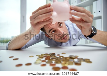business, people, finances, crisis and money saving concept - businessman shaking piggy bank and getting coins at office - stock photo