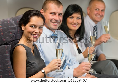 Business people flying airplane drink champagne smiling at camera - stock photo