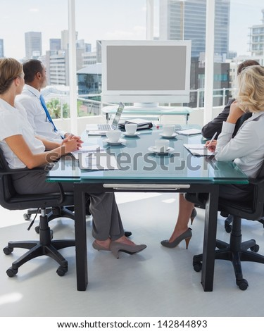 Business people gathered for a video conference in the boardroom - stock photo