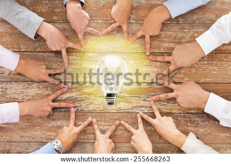 business, people, gesture and inspiration concept - close up of team hands showing victory sign with lighting bulb on table in office - stock photo