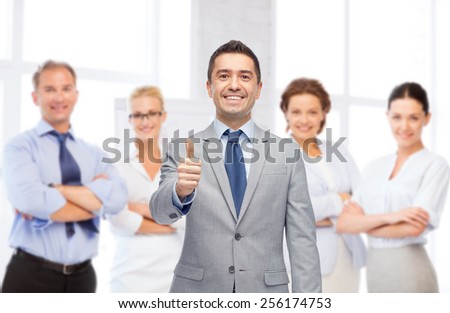 business, people, gesture and office concept - happy businessman with team over office room background showing thumbs up - stock photo