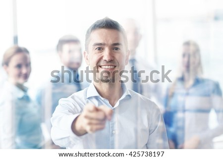 business, people, gesture and teamwork concept - smiling businessman pointing finger to you with group of businesspeople meeting in office - stock photo