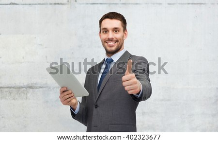 business, people, gesture and technology concept - smiling businessman with tablet pc computer showing thumbs up over gray concrete wall background - stock photo