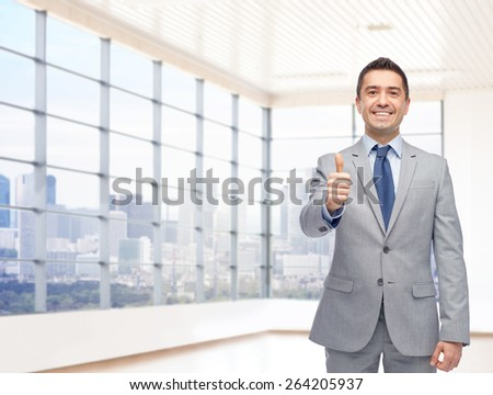 business, people, gesture, real estate and success concept - happy smiling businessman in suit showing thumbs up over city office window background - stock photo