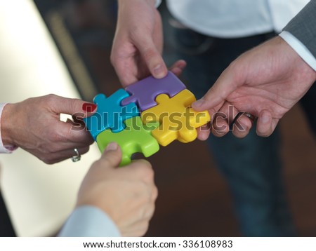 business people group assembling jigsaw puzzle and represent team support and help concept, top view at modern office interior - stock photo