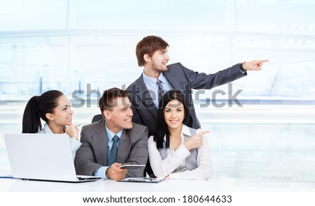 Business people group point finger to side empty copy space, businesswomen businessmen happy smile sitting at office desk, concept of advertisement product - stock photo