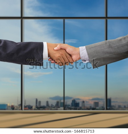 Business people handshaking on background of modern office - stock photo