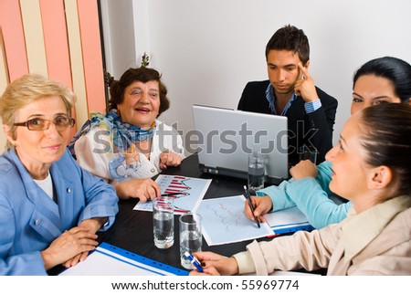 Business people having a funny conversation at meeting and working together,selective focus on elderly laughing woman - stock photo