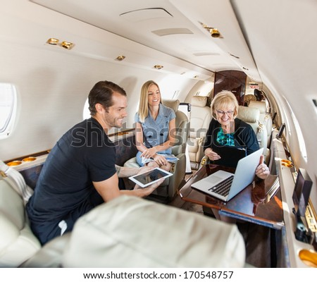 Business people having discussion over laptop on private jet - stock photo