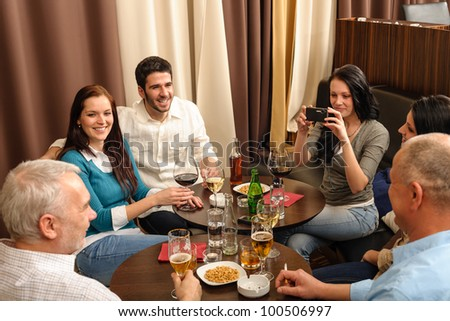 Business people having drink after work taking picture of themselves - stock photo