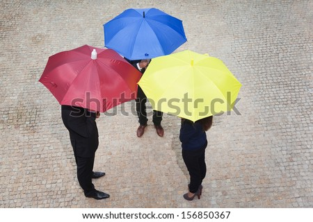 Business people hidden under colorful umbrellas - stock photo