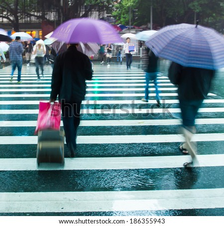 Business people hold umbrellas hurry across the zebra crossing, rainy motion-blurred image - stock photo