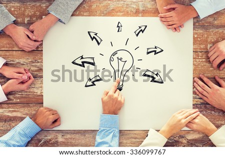 business, people, idea, inspiration and team work concept - close up of creative team sitting at table and pointing finger to bulb doodle on paper in office - stock photo