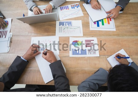 Business people in board room meeting studying some graphics - stock photo