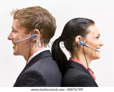 Business people in headsets standing back to back - stock photo