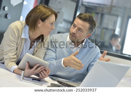 Business people in office working on laptop and tablet - stock photo