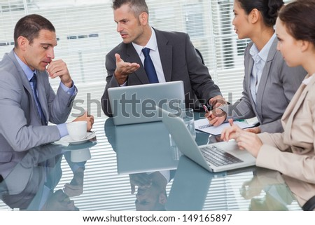 Business people interacting and working together in bright office - stock photo