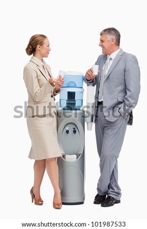 Business people laughing next to the water dispenser against white background - stock photo