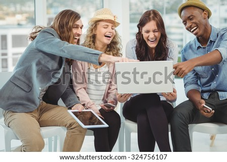 Business people laughing while pointing at laptop in office - stock photo