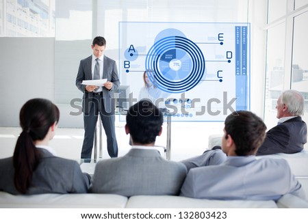 Business people listening and looking at blue diagram interface in a meeting - stock photo