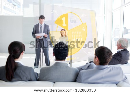 Business people listening and looking at yellow pie chart interface in a meeting - stock photo