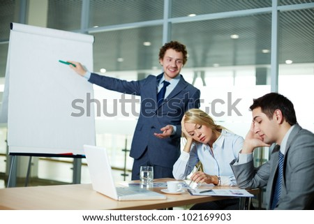Business people listening to presentation, focus is on pensive female - stock photo