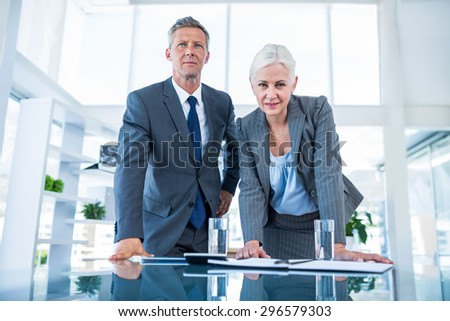 Business people looking at camera behind desk in office - stock photo