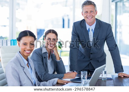 Business people looking at camera in office - stock photo