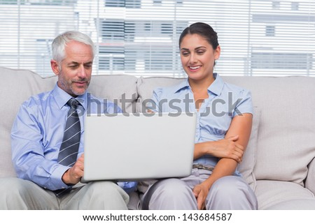 Business people looking at laptop and smiling in staffroom - stock photo
