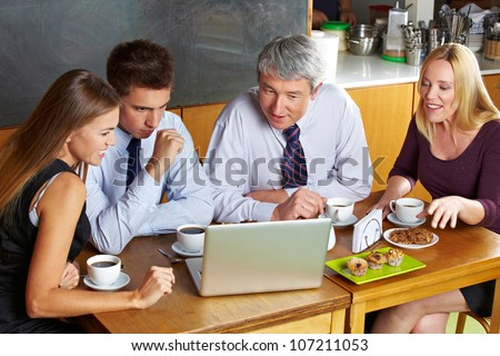 Business people looking at laptop in caf�© during a meeting - stock photo
