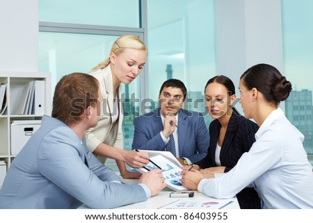 Business people looking at paper with charts - stock photo