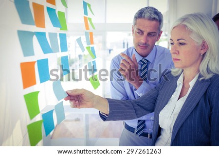 Business people looking at post it on the wall in office - stock photo