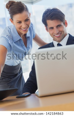 Business people looking the laptop and smiling in the office - stock photo