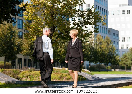 Business people - mature or senior - pass by and greet - stock photo