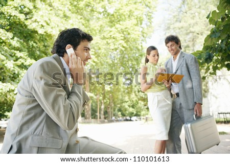 Business people meeting and using technology in the park. - stock photo