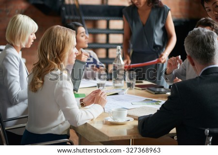 Business people meeting around a boardroom table discussing creative concept - stock photo