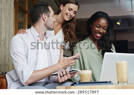 Business people meeting in cafe using laptop drinking coffee - stock photo