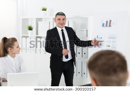 Business people meeting in office to discuss project. Adult businessman pointing to diagram. Business success and teamwork concept - stock photo