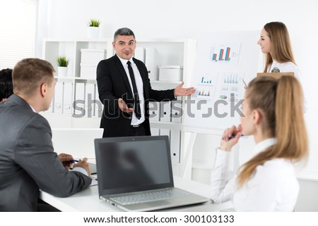 Business people meeting in office to discuss project. Young pretty female office worker looking at camera with her collegues acting on background. Business meeting and teamwork concept - stock photo