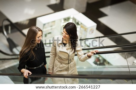 business people on escalator, two young businesswomen talking - stock photo