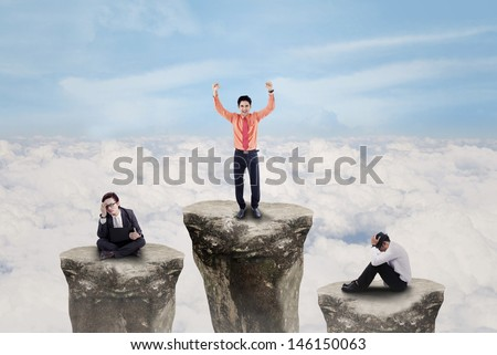 Business people on top of rocks with one winner exulting above clouds - stock photo