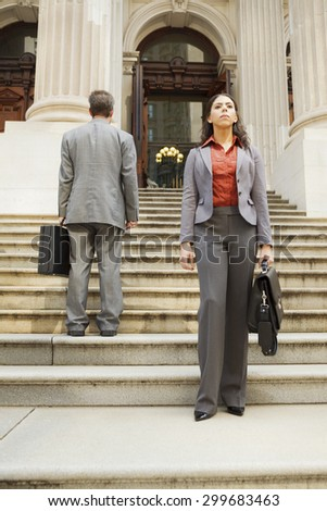 Business people or lawyers on a outdoor staircase. The serious woman facing forwards while the man has his back to the camera. Focus is on woman. - stock photo